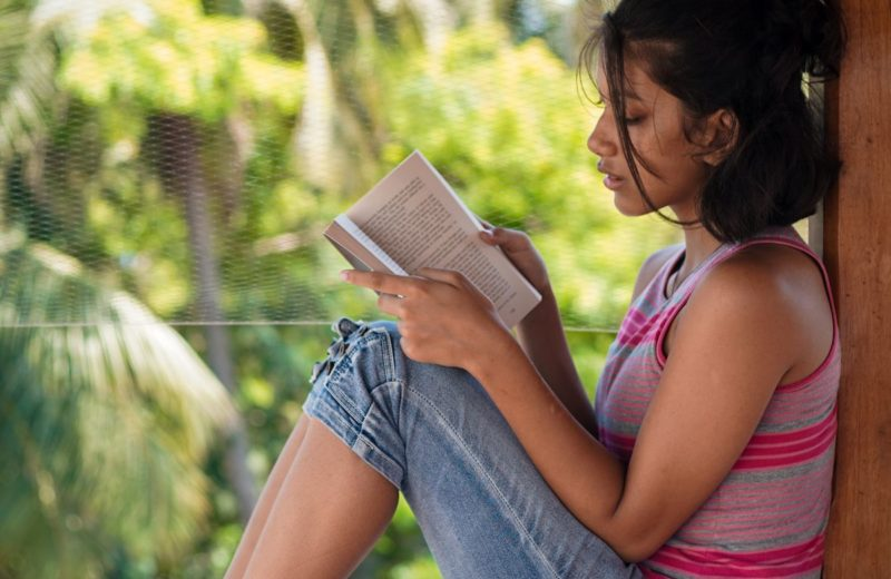 a girl reading a book and lost in imagination as she reads on World Book Day Pondicherry