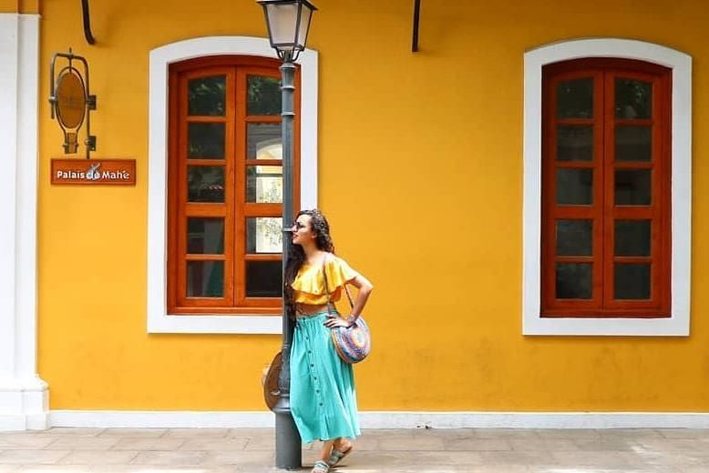 girl posing in white town pondicherry in front of yellow walls Palais de Male and Franco indian architecture